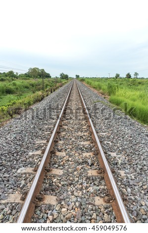 Long straight railroad on concrete sleepers in a rural