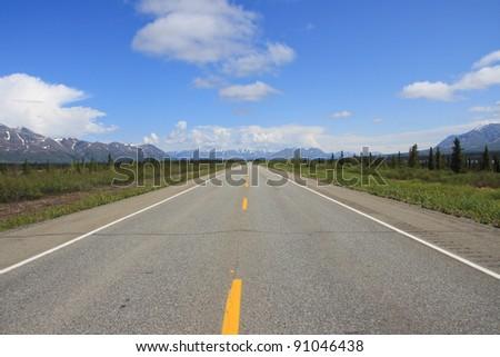 Long straight road in Alaska, near Denali National Park - stock photo
