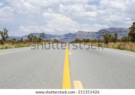 Long street view with mountains in background - stock photo
