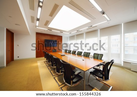 Long table, black armchairs in light room for business meetings.