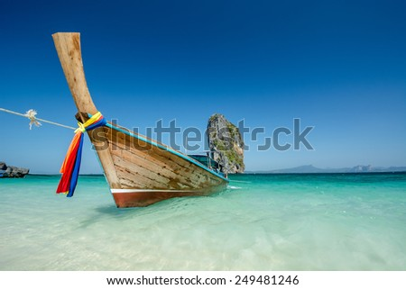 Long tail boats at the beautiful beach landscape in Thailand.   - stock photo