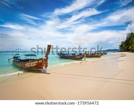 Long-tail boats on the shore of idyllic Bamboo Island, Koh Phi Phi, Thailand.  - stock photo