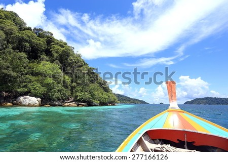 Long tail boats  with crystal clear water, mountains and bright blue sky  at Koh Lipe(Lipe island), Satun, Thailand - stock photo