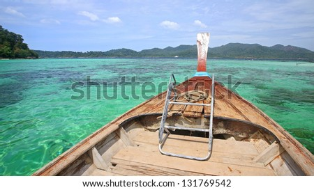 Long tail wooden boat sailing on crystal Andaman sea near Koh Lipe in Satun, Thailand