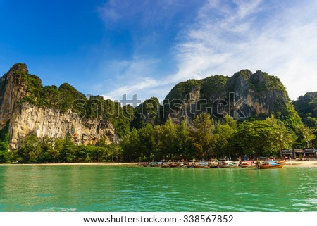 Long-tailed boats moored in a row at a beautiful Railey beach in Krabi, Thailand - stock photo