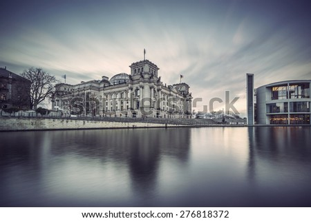 Long time exposure of Reichstag building (seat of German parliament, Bundestag) on river Spree, Berlin Government District, Germany, Europe, Vintage filtered style - stock photo