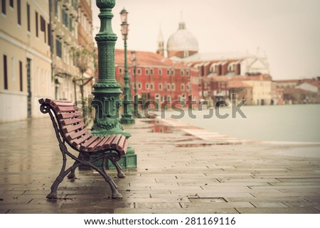 long time exposure of typical wooden bench on promenade in Venice (Venezia) on a rainy day in autumn without people, Italy, Europe, vintage filtered style  - stock photo