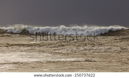 Long wave during a winter sunset before the rain - stock photo