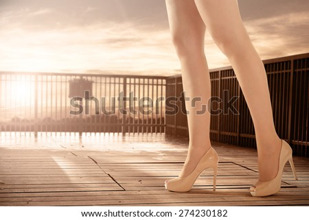 long woman legs with shoes of heels and sunset  - stock photo