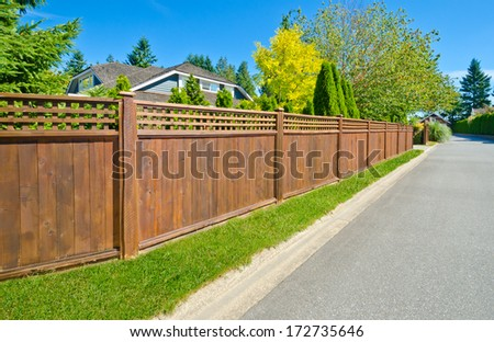 Long wooden cedar fence on the empty street. - stock photo