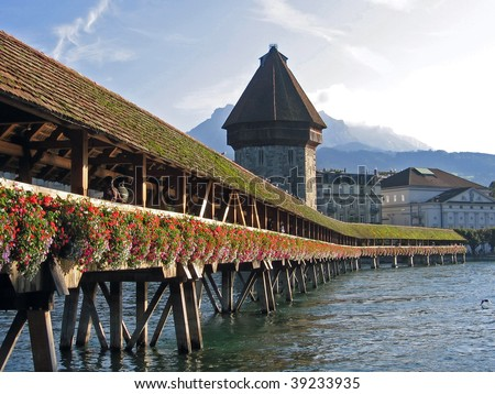 long wooden flower decorated bridge with water tower an city Lucerne in the back