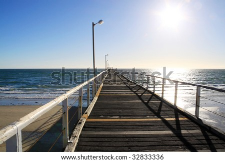 Long Wooden Jetty in Strong Sunlight. Largs Bay Jetty, Adelaide, Australia - stock photo