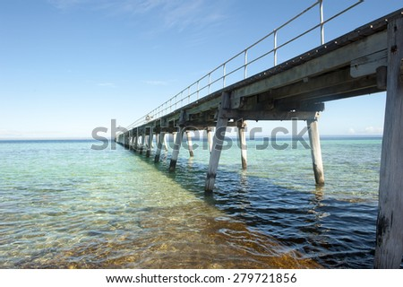 Long wooden jetty over ocean, with blue sky, panoramic view to horizon, copy space.