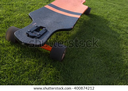 longboard close grass. Black and orange longboard on a green lawn grass
