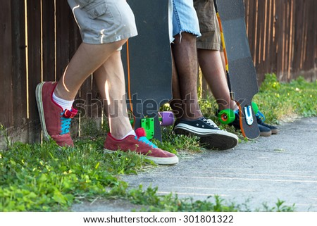 Longboarders feet standing along an urban fence line with their skateboards. Shallow depth of field. - stock photo
