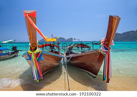 Longtail boats landing in Phi-Phi Island, Thailand - stock photo