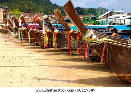 Longtail boats on a beach in row - stock photo
