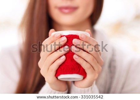 Look at my cute cup. A close up of a girl holding the cup in cute red knitted cupholder with both palms of her hands and smiling on the background.