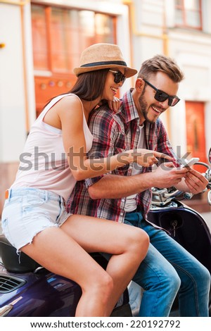Look at that! Beautiful young couple sitting on scooter together while happy woman showing something at mobile phone - stock photo