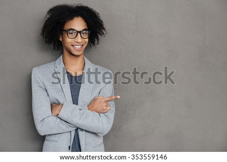 Look at that! Cheerful young African man keeping arms crossed and pointing at copy space while standing against grey background - stock photo