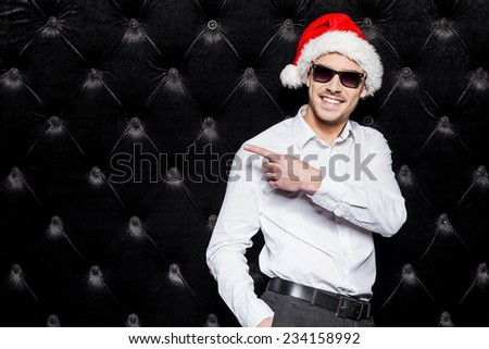 Look at that! Handsome young man in sunglasses and Santa hat pointing away and smiling while standing against black background  - stock photo