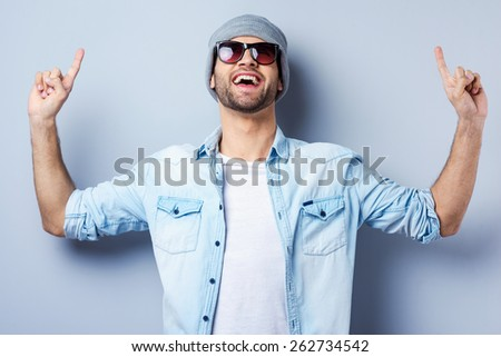 Look at that! Handsome young stylish man in sunglasses and hat pointing up and smiling while standing against grey background - stock photo