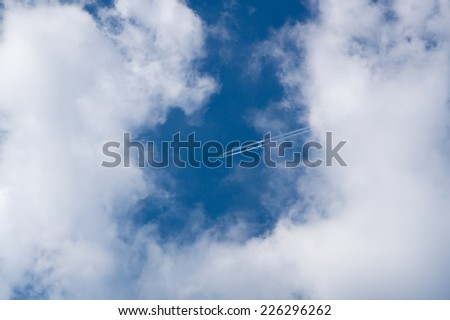 Look at the plane in the clouds... like a clock at 2:10 - stock photo