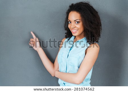 Look at this! Attractive young African woman pointing away and smiling while standing against grey background  - stock photo