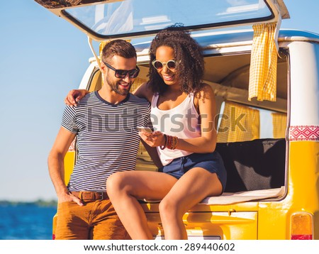 Look at this photo! Cheerful young couple looking at mobile phone together while both sitting at the trunk of retro minivan with sea in the background  - stock photo