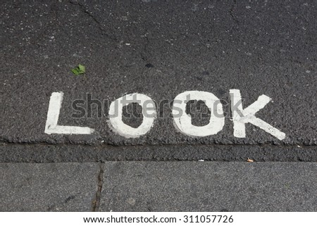 Look before crossing, sign on the asphalt road - stock photo