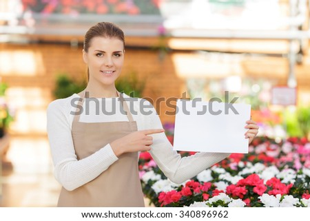 Look her. Nice attractive seller of flowers holding sheet of paper and pointing it while being involved in work - stock photo