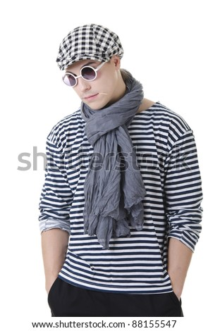 Look naughty handsome young man in stylish striped dress, glasses and cap with suitcase