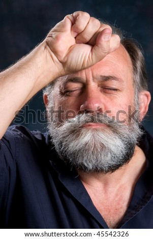 Look of disappointment on a man's face with his fist clenched on the forehead. - stock photo