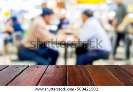 Look out from the table, blur image of group of elderly men are eating in restaurant as background.