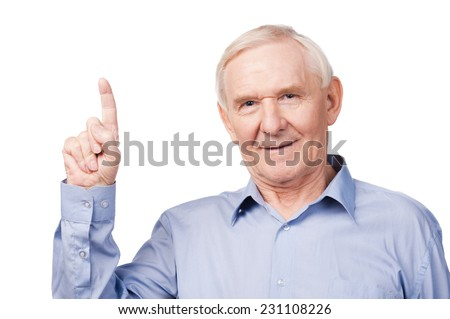 Look over there! Cheerful senior man pointing up and smiling while standing against white background - stock photo
