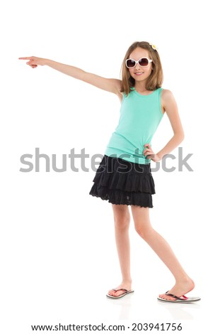 Look there! Young girl in teal shirt and black skirt pointing. Full length studio shot isolated on white. - stock photo