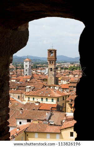 Look through a window onto two towers of the city of Lucca in Tuscany, Italy, from inside the the Guinigi tower - stock photo