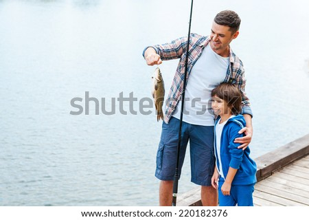 Look what we caught! Father holding fishing rod and showing big fish to his son  - stock photo