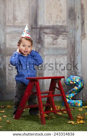 Look who's two!  Adorable toddler standing next to a red ladder with a party hat on the ground and a number two in the background. - stock photo