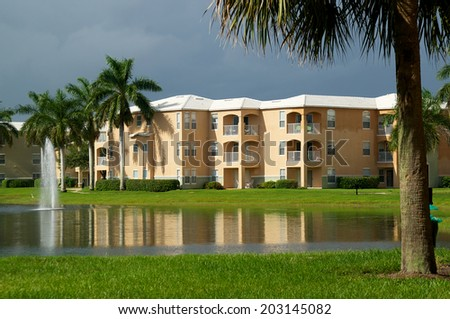 Looking across a pond towards a three story apartment complex in Naples, Florida, with a stormy sky and sunlight on buildings.