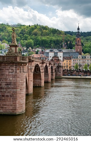 Looking Across Neckar River at Old Bridge Leading to Old Town Heidelberg, Baden-Wurttemberg, Germany with Clouds Overhead - stock photo