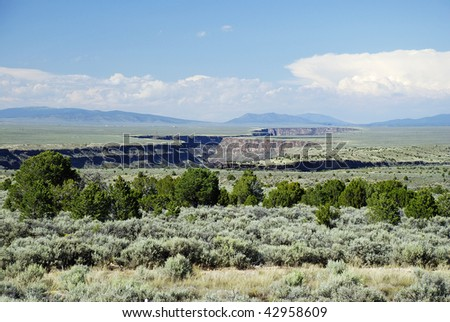 Looking across the Taos Plateau at the  Rio Grande Gorge with hazy mountains, blue sky and puffy clouds in background. - stock photo