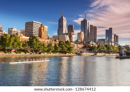Looking across the Yarra River from Southbank with early morning rowers training - stock photo