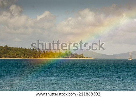 Looking at a rainbow from Tropical Daydream Island which is part of the Whitsunday Islands - stock photo