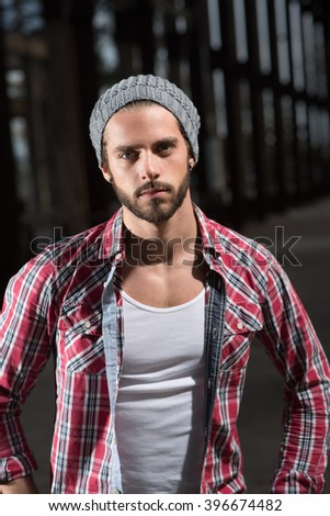 Looking at camera, handsome trendy young guy in the street with a cool attitude. he wears beard and a plaid shirt
