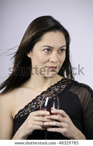 Looking away from the camera and holding a glass wine. She is of mixed ethnicity. - stock photo