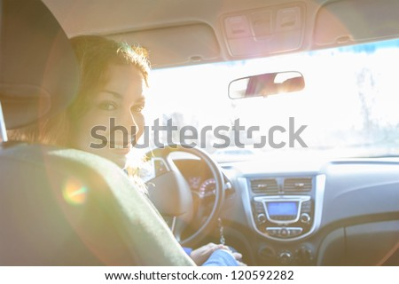 Looking back and sitting inside of car woman with sun rays in window - stock photo