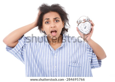 Looking disheveled. Attractive young mulatto lady standing with opened mouth against isolated background and holding little alarm clock. - stock photo