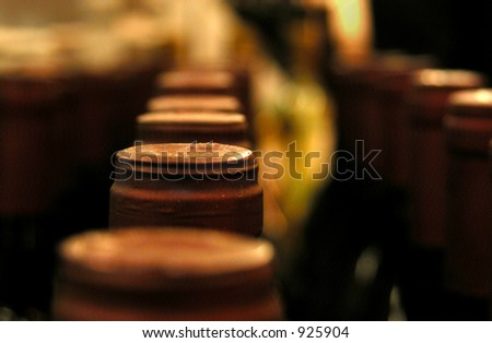 looking down a line of wine bottle tops - stock photo