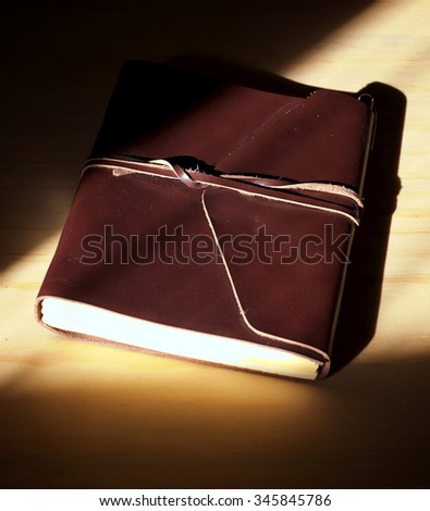 Looking down at a closed and tied brown leather journal lit by morning sun making the edge of the book seem to glow.